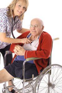 elderly man in wheelchair and woman nurse checking pulse stock photo